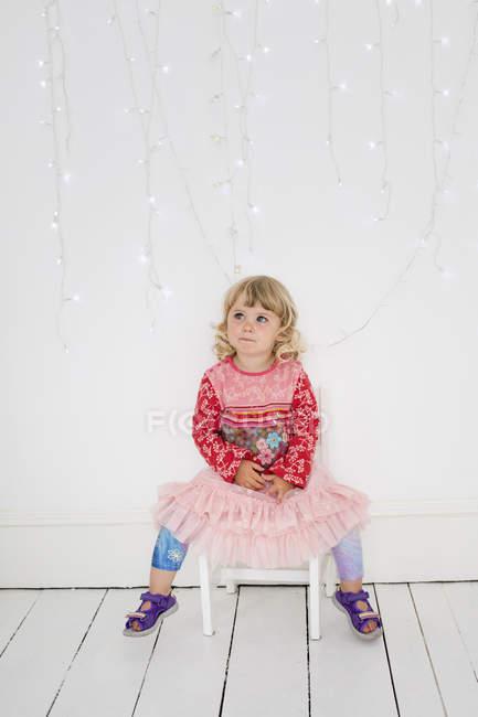 Junges Mädchen sitzt auf einem Stuhl — Stockfoto