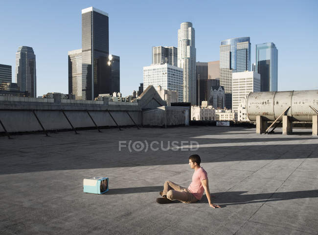 Man sitting on a city rooftop — Stock Photo