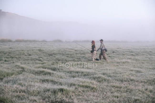 Gente caminando a través de un prado - foto de stock