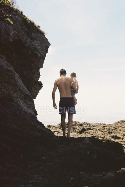 Man carrying son across rocks — Stock Photo