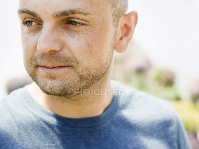 Man with stubble in a blue tee sirt — Stock Photo