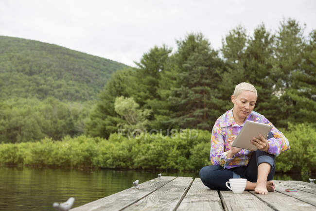 Woman sitting on jetty using tablet — Stock Photo