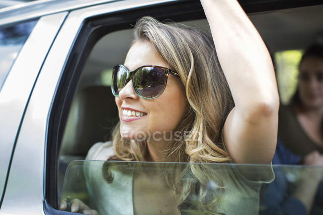 Young woman leaning out of a car — Stock Photo