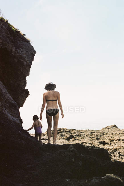 Woman walking with daughter across rocks — Stock Photo