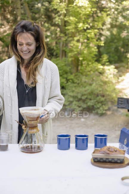 Mulher em um jardim, fazendo café . — Fotografia de Stock