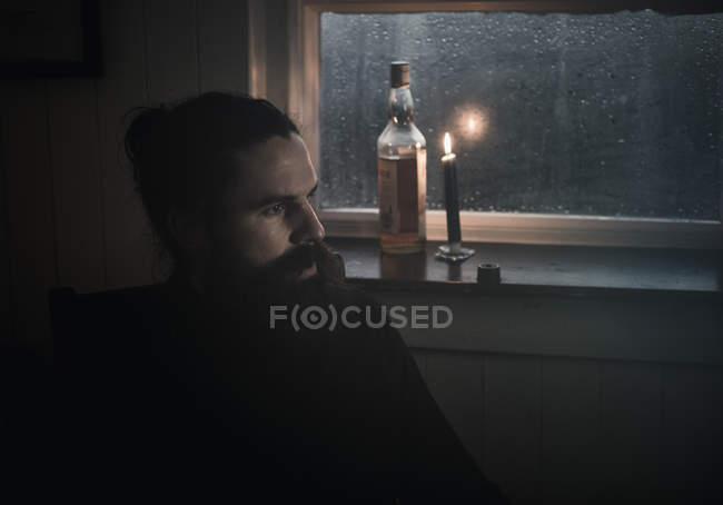 Uomo che si siede nel buio di una finestra — Foto stock