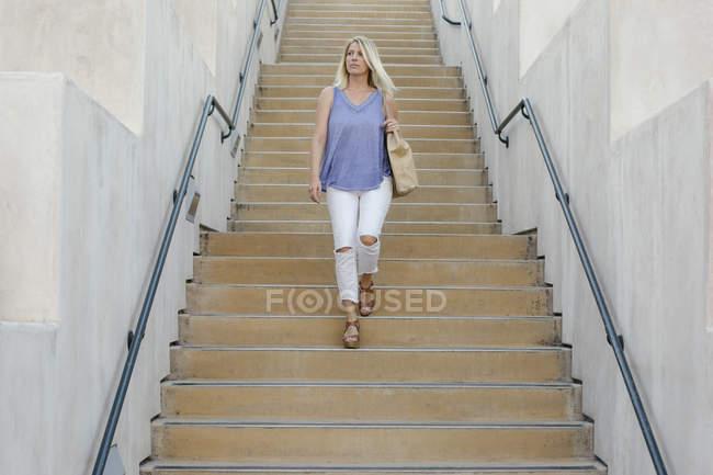 Blond woman walking down — Stock Photo