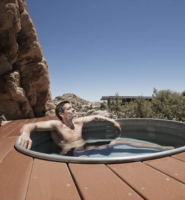 Man on the terrace in a sunken hot tub. — Stock Photo