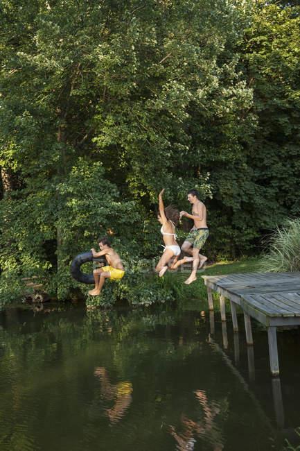 Pulando do cais água de meninos — Fotografia de Stock