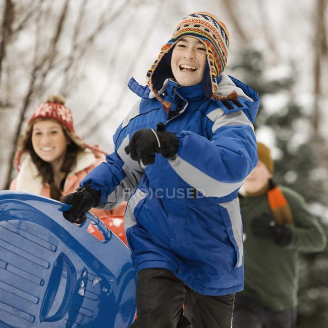 Children running, carrying sledges. — Stock Photo