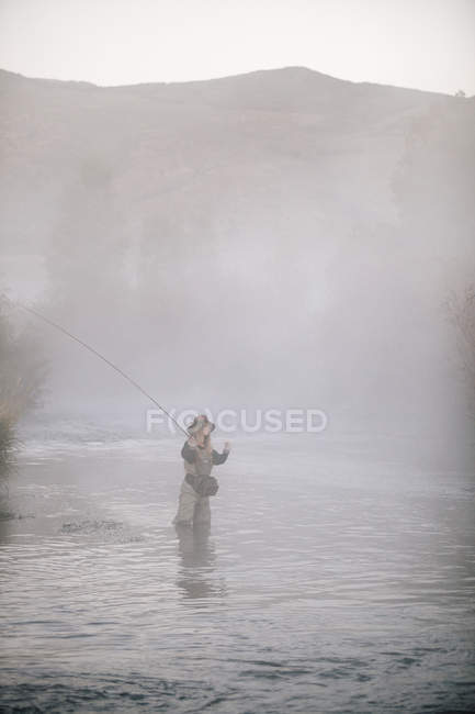 Woman flyfishing in water. — Stock Photo