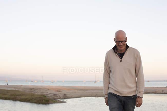 Homem careca andando em uma praia de areia — Fotografia de Stock
