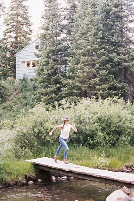 Woman running across a wooden bridge — Stock Photo