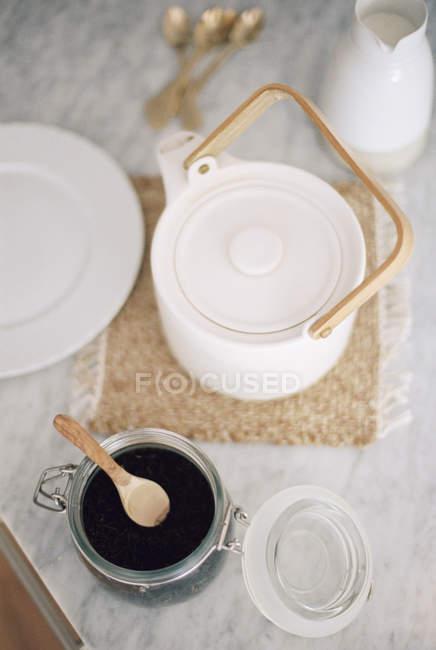 Vaso con foglie di tè e teiera — Foto stock
