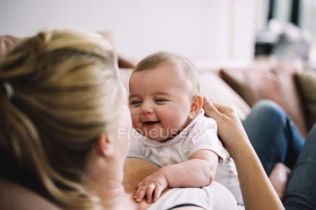 Mulher deitada em um sofá com bebê menina . — Fotografia de Stock