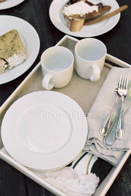 Bandeja con tazas, platos y cubiertos - foto de stock