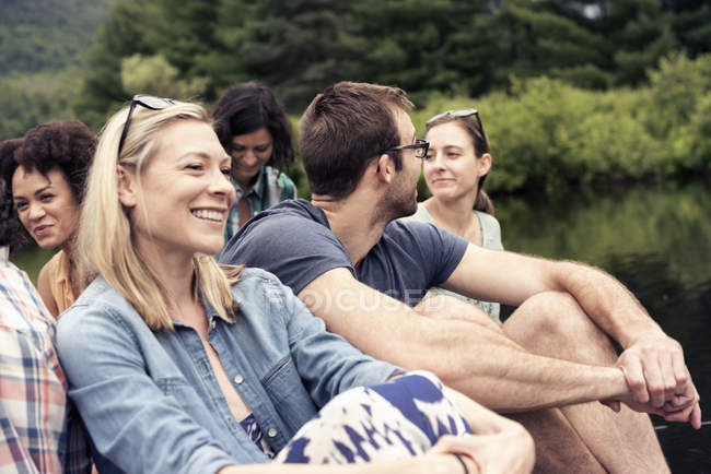 Group of women and men seated by a lake — Stock Photo