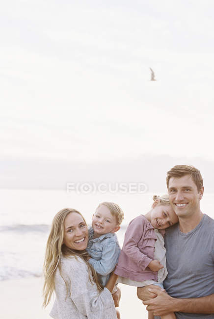 Família em uma praia de areia junto ao oceano — Fotografia de Stock