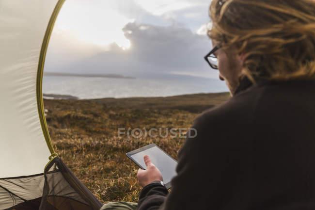 Homem na tenda segurando um tablet digital — Fotografia de Stock