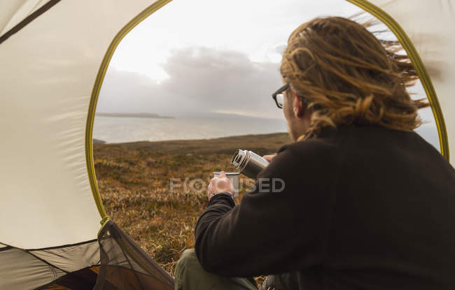 Man sitting in the shelter of a tent — Stock Photo