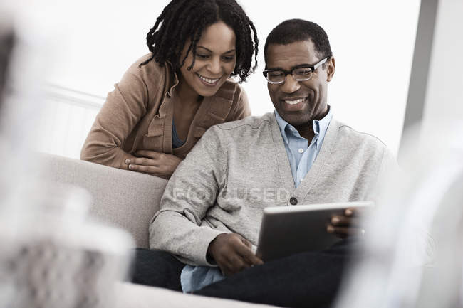 Man and woman using a digital tablet. — Stock Photo