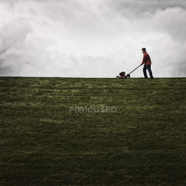 Man mowing the grass on a property — Stock Photo