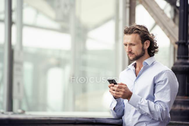 Uomo che controlla il cellulare all'aperto — Foto stock