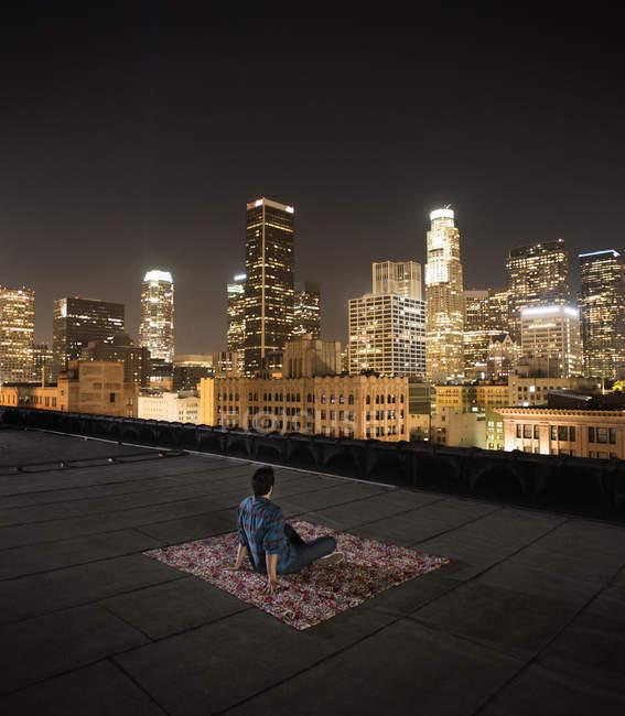 Homme assis sur un tapis sur un toit — Photo de stock
