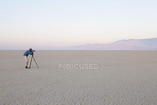 Человек с камерой и штатив — стоковое фото