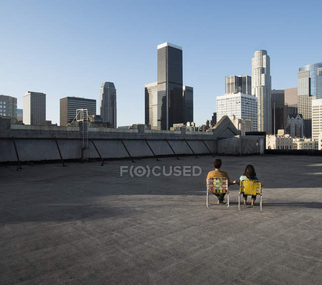 Couple on a rooftop overlooking city skyscrapers — Stock Photo