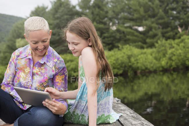 Femme et fille utilisant une tablette numérique — Photo de stock