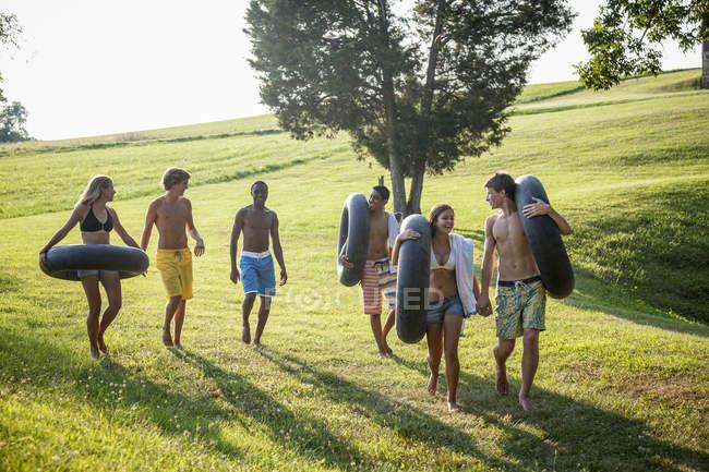 Ragazzi e ragazze, in possesso di asciugamani e galleggianti — Foto stock
