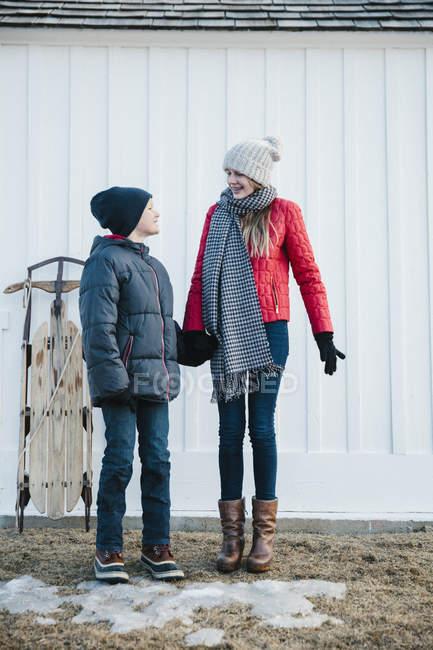 Children standing in winter coats in a yard. — Stock Photo
