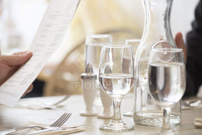Wine and water glasses and place settings at a table — Stock Photo