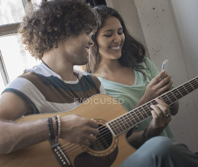 Man playing guitar and a woman with phone — Stock Photo
