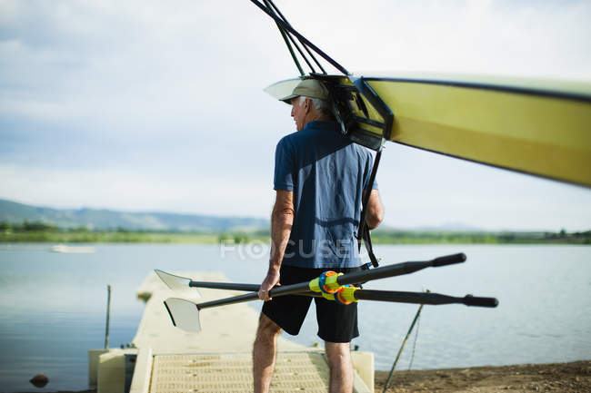 Man carrying oars and rowing shell — Stock Photo