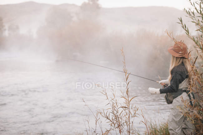 Mulher nas margens de um rio, pesca com mosca . — Fotografia de Stock