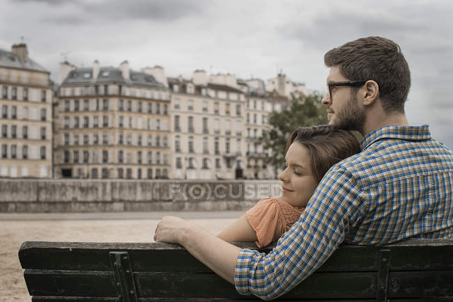 Couple sitting on a bench by the River Seine. — Stock Photo