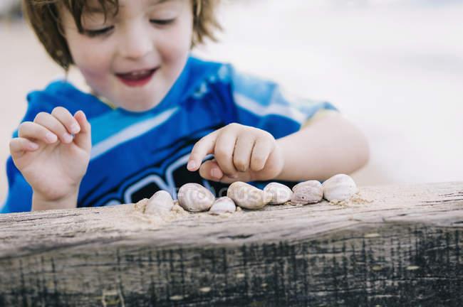 Хлопчик на пляжі підрахунку волоського горіха — стокове фото