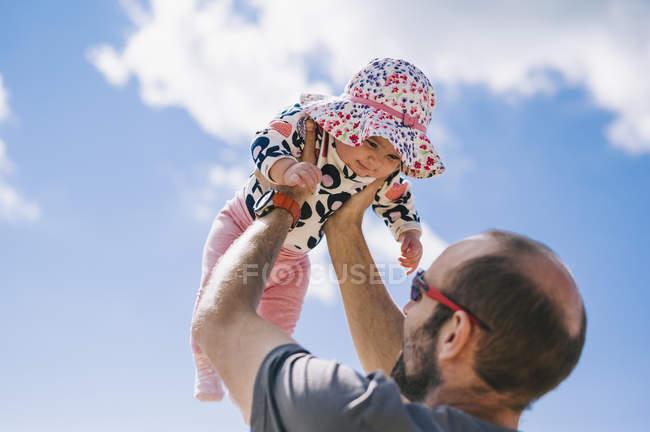 Père soulevant sa fille bébé — Photo de stock