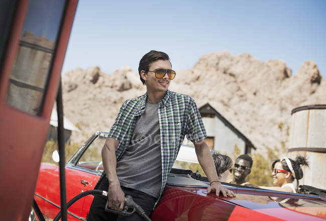 Man filling a red convertible car — Stock Photo