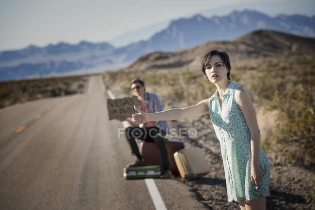 Pareja en camino en el desierto hitchiking - foto de stock