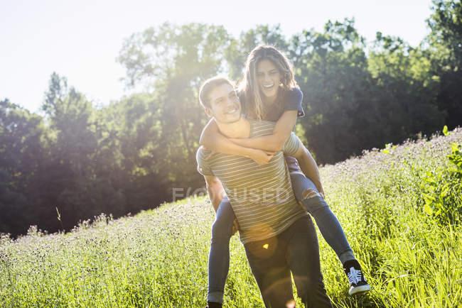 Hombre dando mujer un piggyback en prado - foto de stock