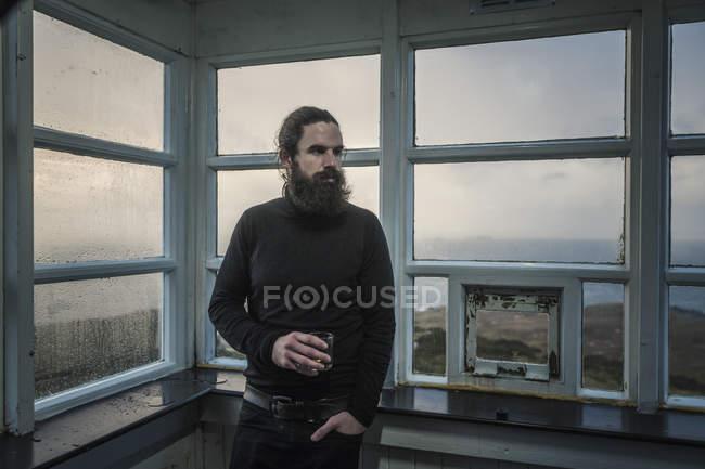 Uomo in piedi in una finestra — Foto stock