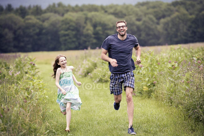 Man and child running through meadow — Stock Photo