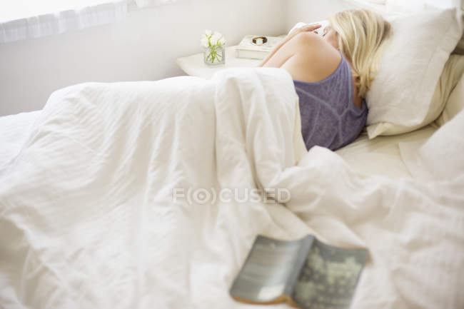 Woman sleeping in a bed — Stock Photo