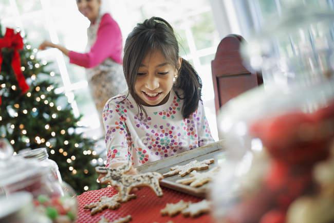 Niña decorando galletas con glaseado - foto de stock