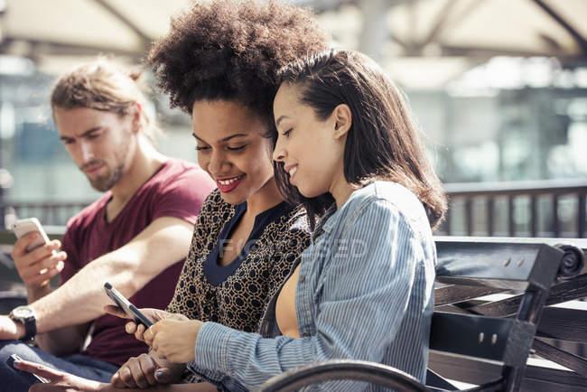 Три человека проверяют свои смартфоны — стоковое фото