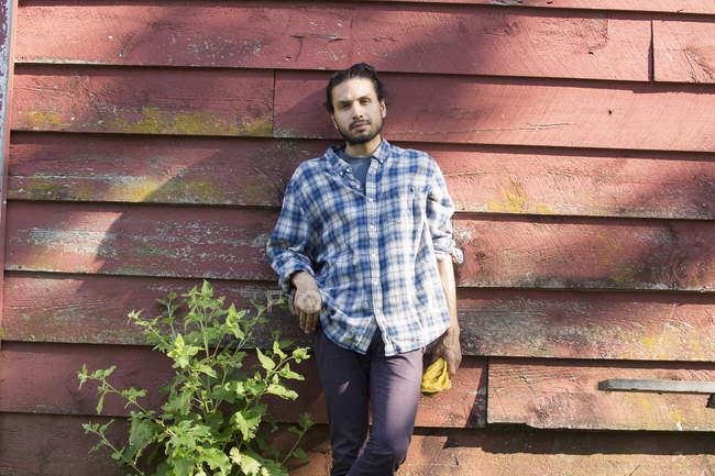Человек прислонился к деревянной стене — стоковое фото