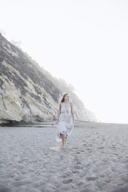 Woman walking on a sandy beach — Stock Photo